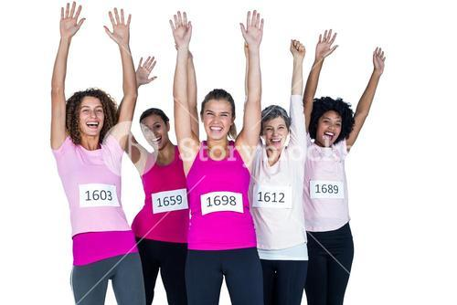 Portrait of happy female athletes with arms raised