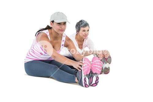 Women touching toes while exercising