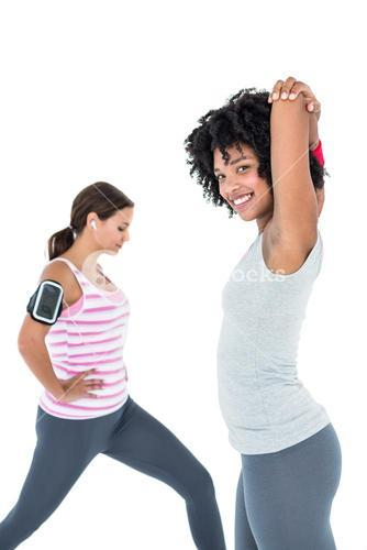 Woman exercising while female friend stretching