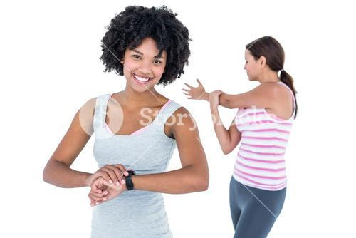 Woman wearing wristwatch while female friend exercising