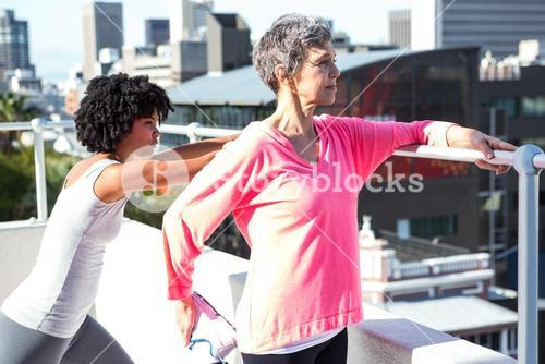 Mature woman stretching with female friend by railing