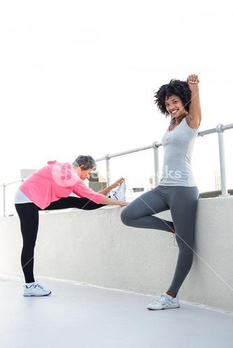 Happy young woman stretching with female friend