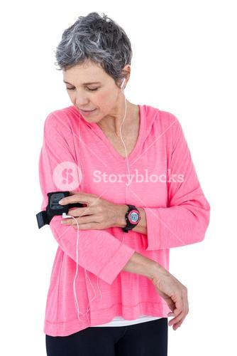 Woman adjusting armband while listening music