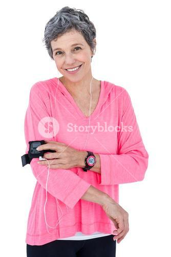 Portrait of happy woman using mp3 player in armband