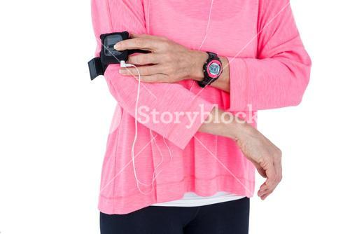 Mid section of woman using mp3 player in armband