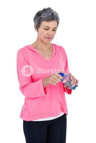 Mature woman opening water bottle while listening music