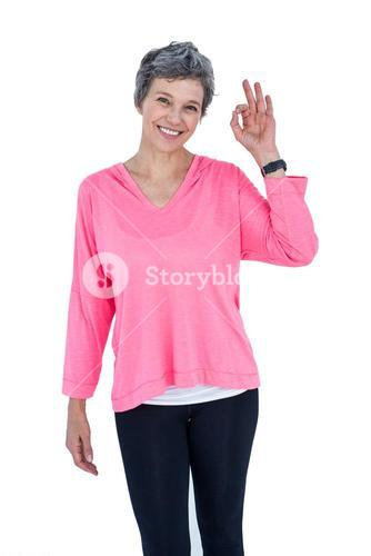 Portrait of cheerful mature woman showing OK sign