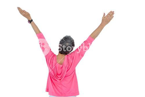 Rear view of mature woman with arms raised