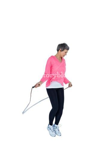 Mature woman exercising with jump rope