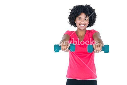 Portrait of happy young woman exercising with dumbbells