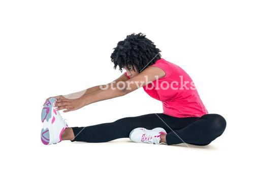 Young woman touching toes while exercising