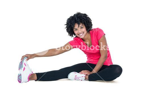 Portrait of young woman touching toes while exercising