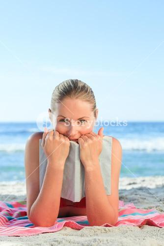 Adorable woman posing with a book on the beach