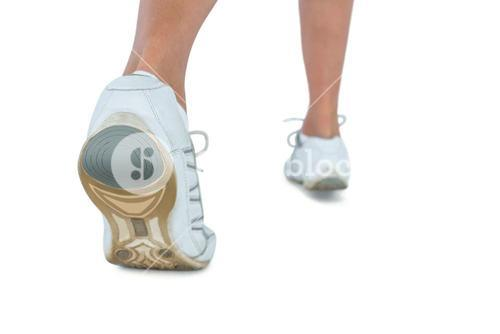 Low section of woman wearing sports shoe jogging