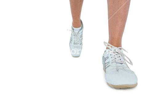 Low section of woman wearing sports shoe running