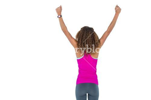 Rear view of young woman cheering with arms raised