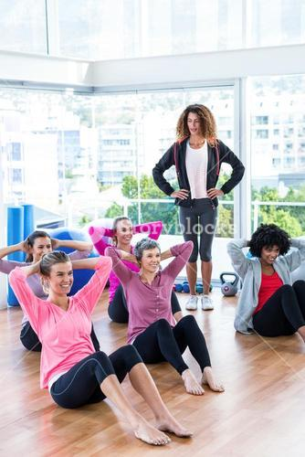 Female trainer assisting women in sit ups