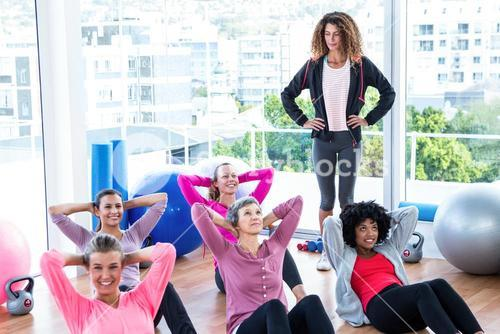 Young female trainer assisting women sit ups