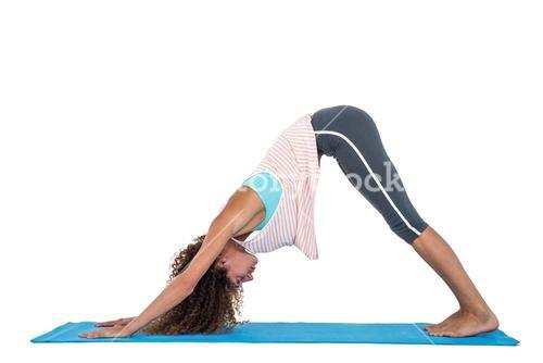 Young woman in downward facing dog position