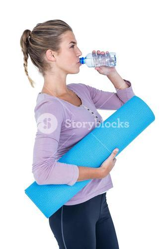 Woman drinking water while holding exercise mat