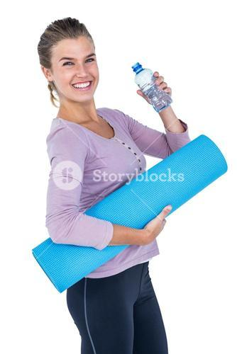 Woman holding water bottle and exercise mat