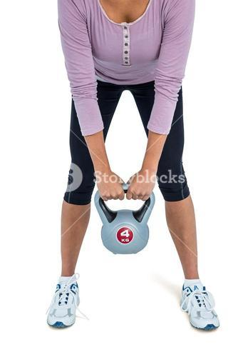 Low section of woman exercising with kettlebell