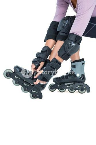 Low section of sporty woman wearing inline skates
