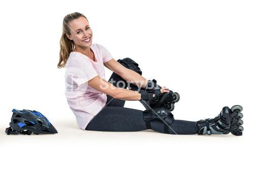 Portrait of cheerful sporty woman wearing inline skates