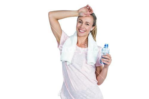 Sporty woman touching forehead while holding bottle