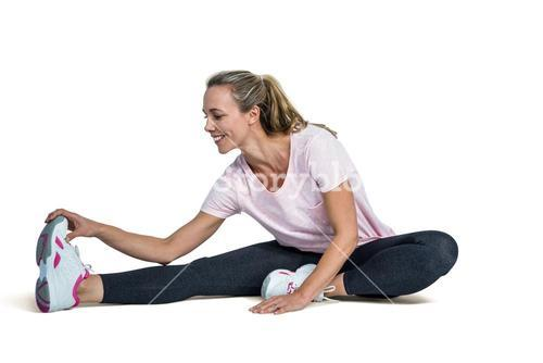 Happy woman touching toes while exercising