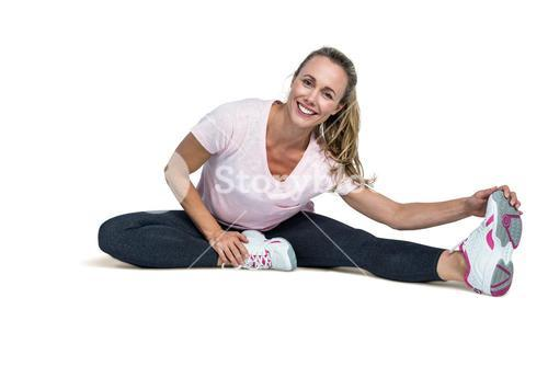 Cheerful woman touching toes while exercising