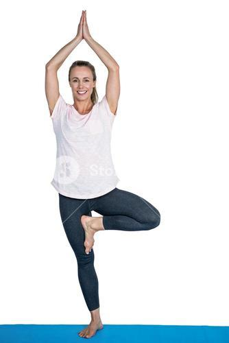 Portrait of happy fit woman in tree pose
