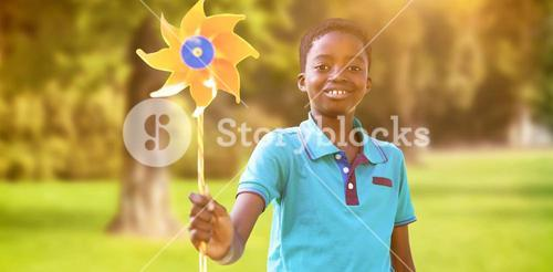 Composite image of happy boy in the park with pinwheel