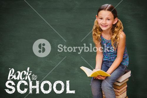 Composite image of cute little girl reading book in library