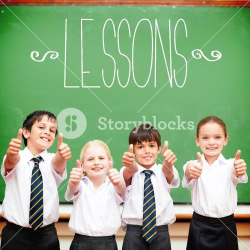Lessons against cute pupils showing thumbs up in classroom