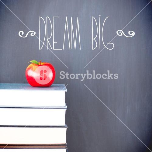 Dream big against red apple in front of blackboard on books