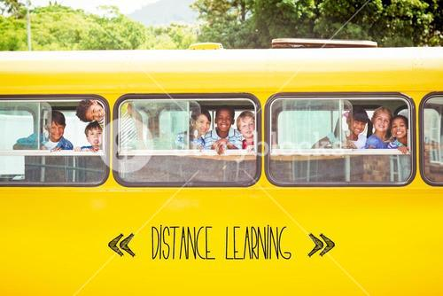 Distance learning against cute pupils smiling at camera in the school bus