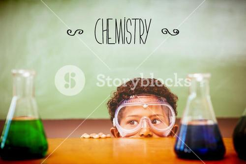 Chemistry against boy looking at conical flasks in classroom