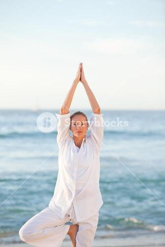 Woman practicing yoga against the sea
