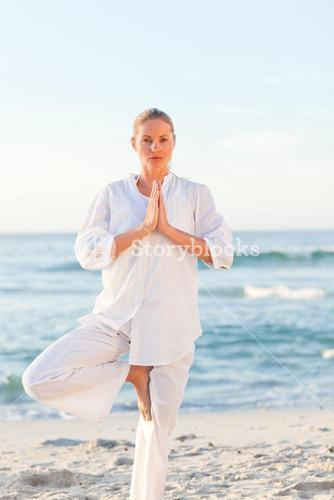 Active woman practicing yoga on the beach against the sea