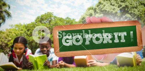 Go for it! against children lying on grass and reading books