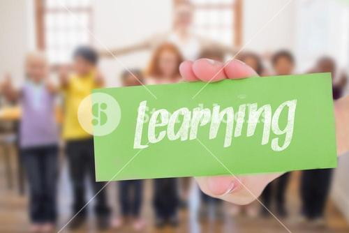 Learning against teacher and pupils smiling at camera in classroom