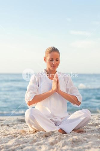 Peaceful woman practicing yoga against the sea
