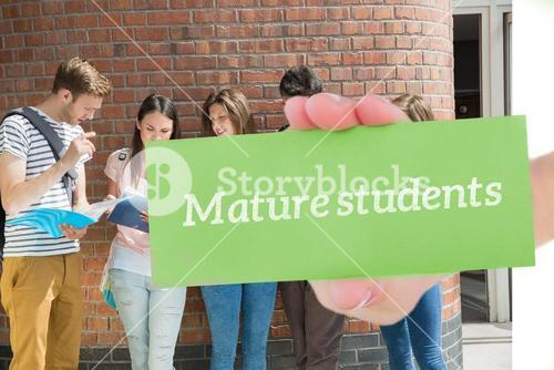 Mature students against happy students standing and reading