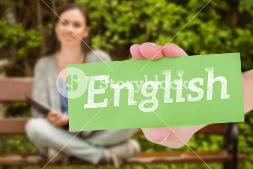 English against smiling student sitting on bench listening music with mobile phone and holding book