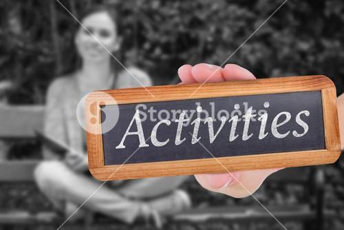 Activities against smiling student sitting on bench listening music with mobile phone and holding bo