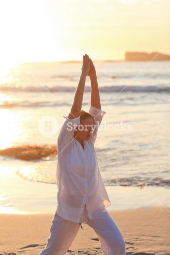 Woman practicing yoga during the sunset against the sea