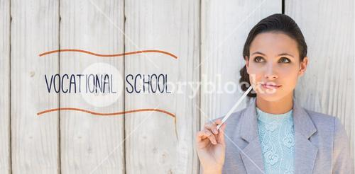 Vocational school against stylish brunette thinking and smiling