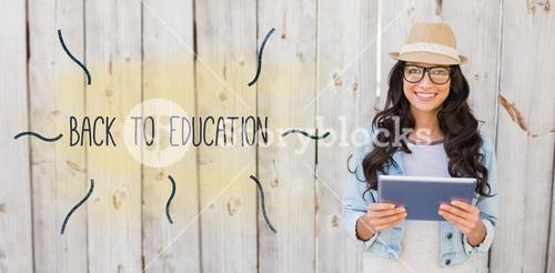 Back to education against pretty hipster smiling at camera holding tablet