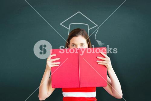 Composite image of student holding book over face